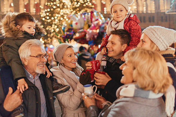 family on christmas market - christmas families stock photos and pictures