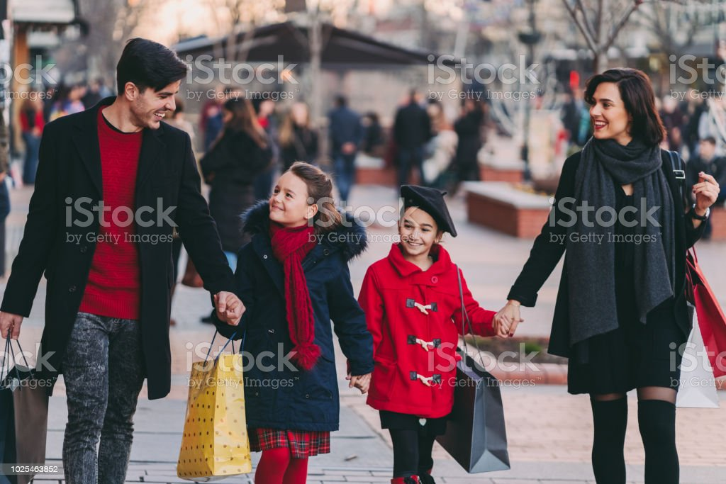 Happy family with two kids shopping gifts for the Christmas holidays