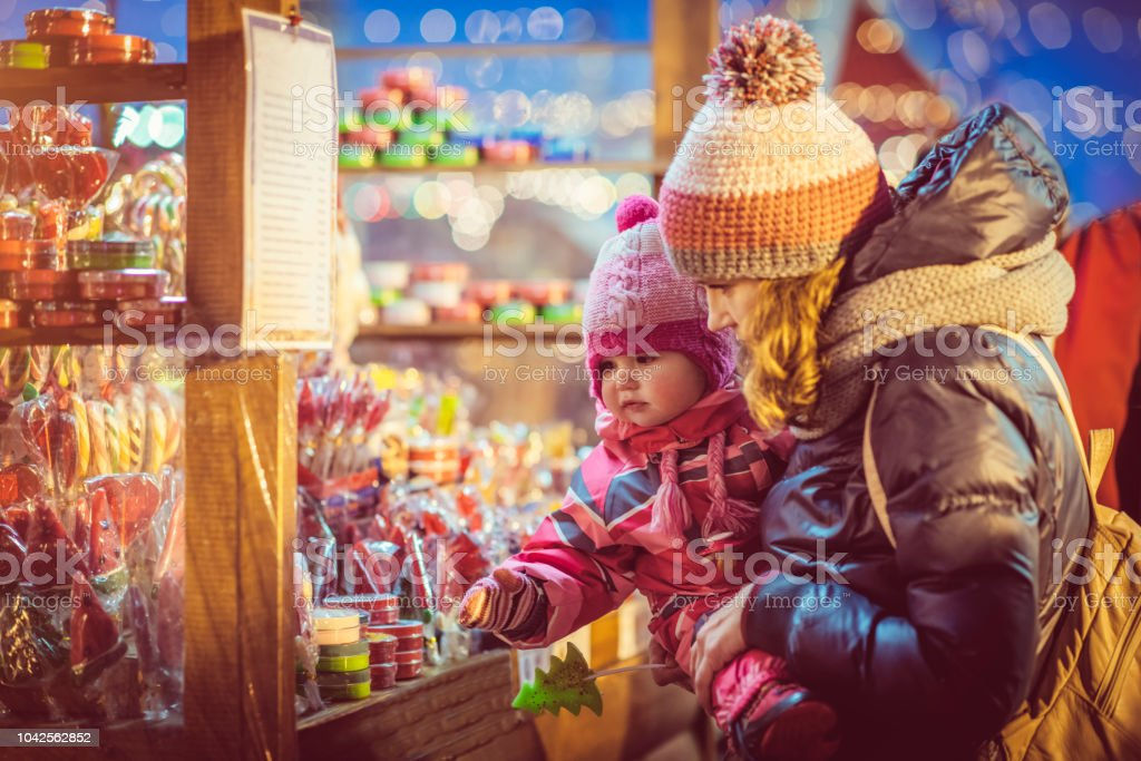 Mother and daughter enjoying Christmas time at market