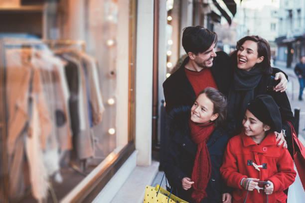 familie auf weihnachts-shopping - günstige weihnachtsgeschenke stock-fotos und bilder