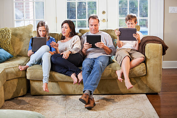 Family on couch, using digital tablets stock photo