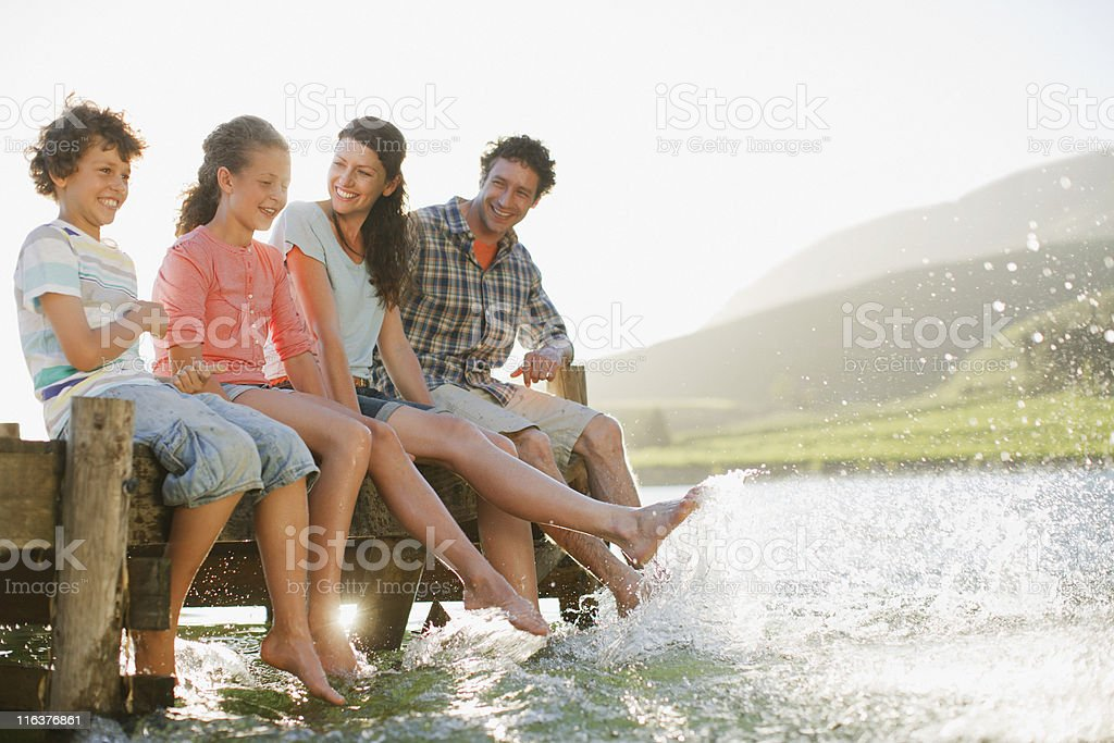 Family on dock splashing feet in lake stock photo