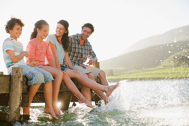 familie am dock planschen füße in lake - kinderfüße stock-fotos und bilder