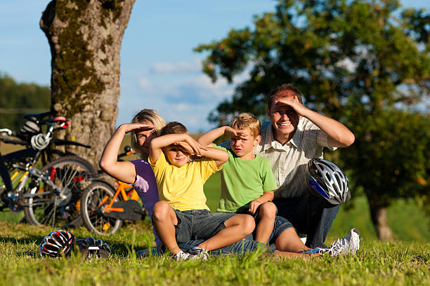 Family on getaway with bikes Happy family (father, mother and two sons) on getaway with bikes - they have a break dazzled stock pictures, royalty-free photos & images