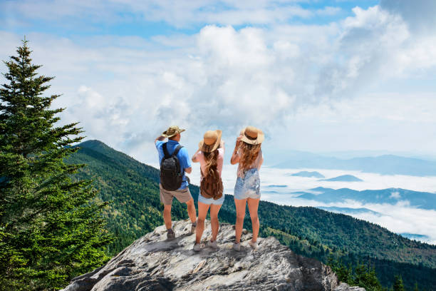 Family on hiking trip, standing on top of the mountain over the clouds. stock photo