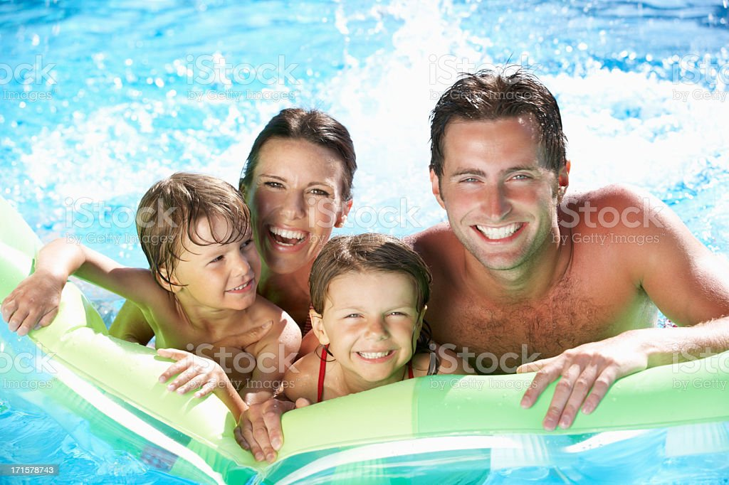 Family On Holiday In Swimming Pool stock photo