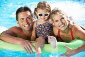 Family On Holiday In Swimming Pool Smiling To Camera.