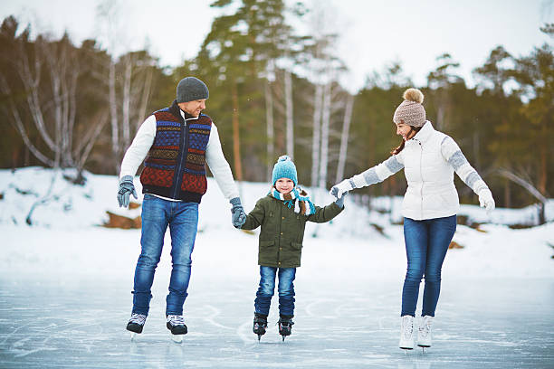 Family on ice-rink Modern family of father, mother and son skating in natural environment ice skating stock pictures, royalty-free photos & images