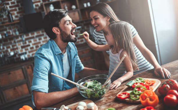 Family on kitchen Mom, dad and daughter are cooking on kitchen. Happy family concept. Handsome man, attractive young woman and their cute little daughter are making salad together. Healthy lifestyle. eating stock pictures, royalty-free photos & images