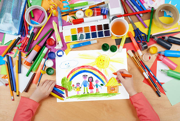 family on meadow with rainbow and house child drawing family on meadow with rainbow and house child drawing, top view hands with pencil painting picture on paper, artwork workplace cartoon and kids stock pictures, royalty-free photos & images