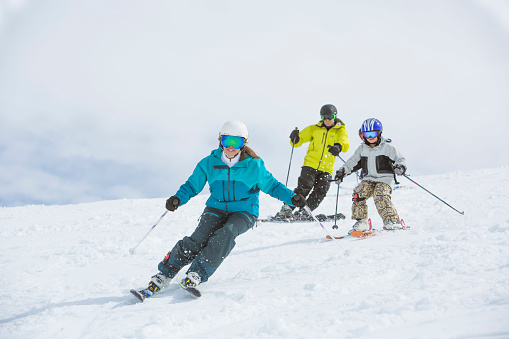 Family skiing together on sunny day.