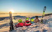 Happy family is lying on snow and watching on sunset from top of the mountain