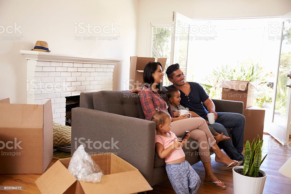 Family On Sofa Taking A Break From Unpacking Watching TV stock photo