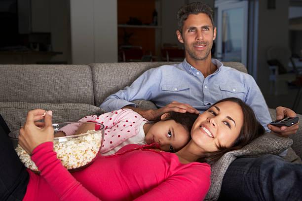 familie auf sofa vor dem fernseher und essen popcorn - mädchen night snacks stock-fotos und bilder