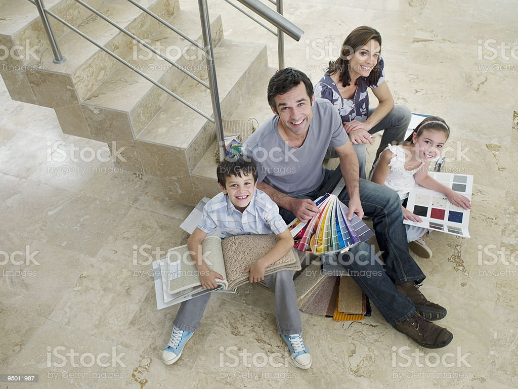 Family on staircase looking at paint and carpet samples stock photo