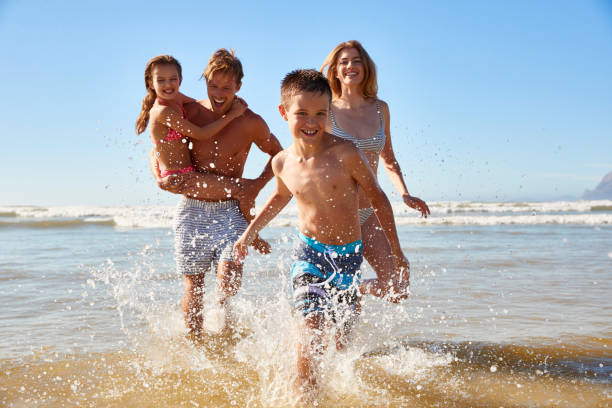 Family On Summer Beach Vacation Run Out Of Sea Towards Camera stock photo