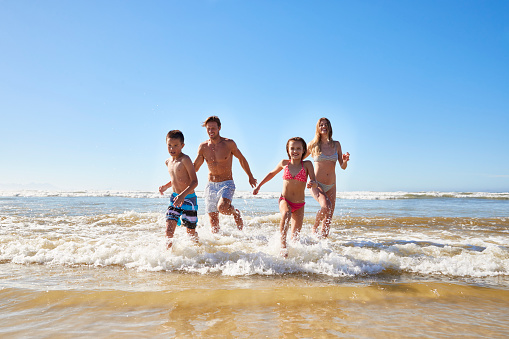 istock Family On Summer Beach Vacation Run Out Of Sea Towards Camera 935360512
