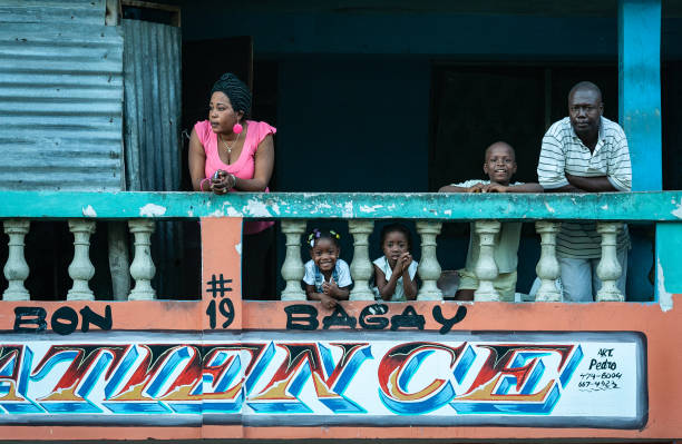 Family on the balcony. Cap-Haïtien, Haiti - January 12, 2009 : Haiti is recognized as one of the poorest countries on Earth. More than 80 per cent of the population lives below the poverty line. haitian ethnicity stock pictures, royalty-free photos & images