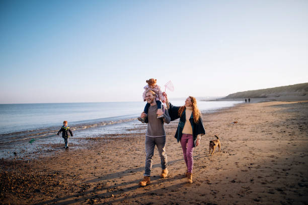 Family on the Beach During Winter Three generation family enjoying walking along the coast. Its cold outside so they are wrapped up warm. cumbria stock pictures, royalty-free photos & images