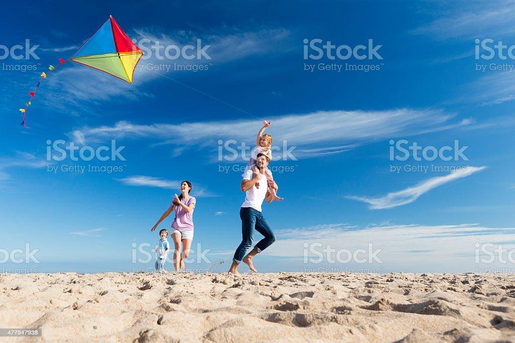 Famille sur la plage Flting un cerf-volant - Photo