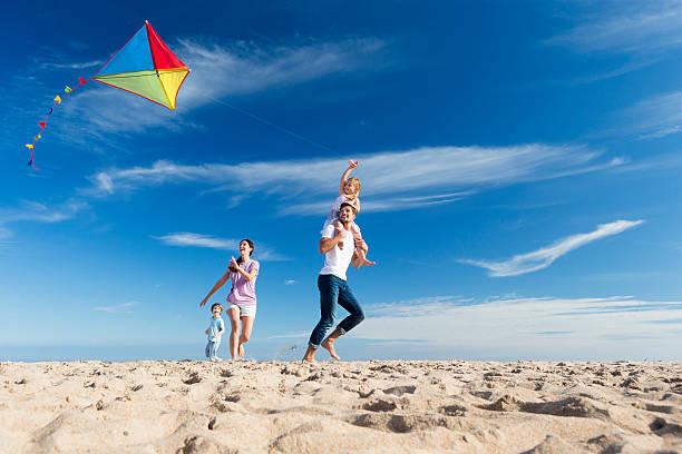 Family on the Beach Flting a Kite stock photo