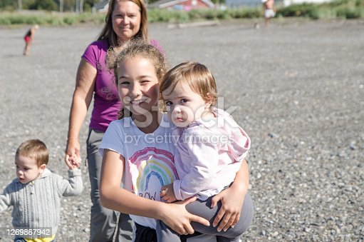 Family walking on the beach of the St. Lawrence river during summer day in Gaspesie (Les Mechins)