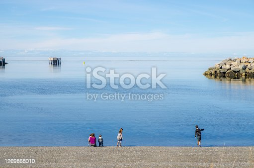 Family on the beach of the St. Lawrence river during summer day in Gaspesie (Les Mechins)