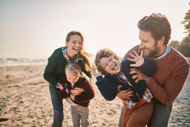 family on the beach - four people stock photos and pictures