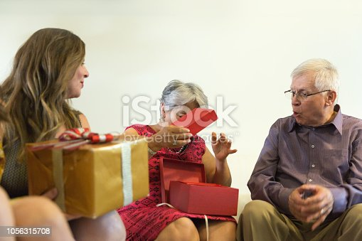 istock Family on the living room exchancing christmas presents in Brazil - amigo secreto 1056315708