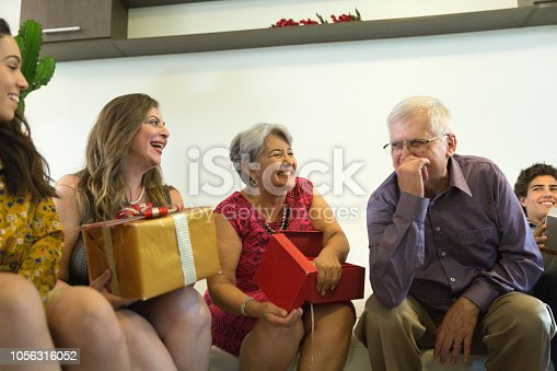 istock Family on the living room exchancing christmas presents in Brazil - amigo secreto 1056316052