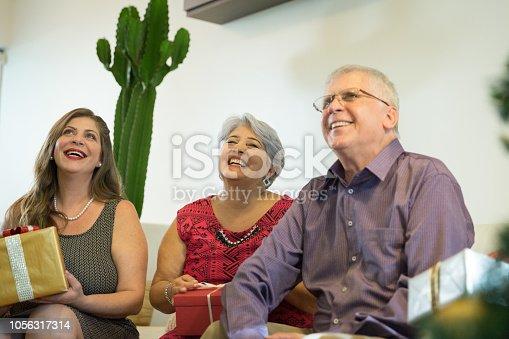 istock Family on the living room exchancing christmas presents in Brazil - amigo secreto 1056317314