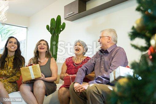 istock Family on the living room exchancing christmas presents in Brazil - amigo secreto 1056317668