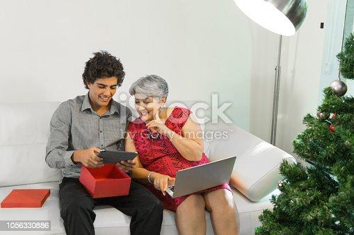 istock Family on the living room exchancing christmas presents in Brazil - amigo secreto 1056330886