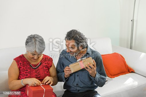 istock Family on the living room exchancing christmas presents 1056327532