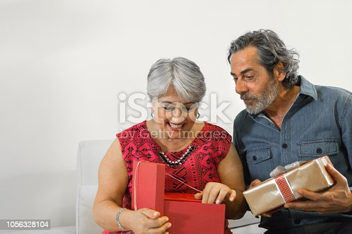istock Family on the living room exchancing christmas presents 1056328104