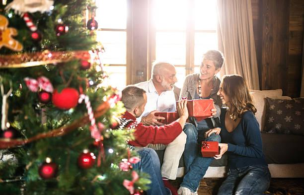 familie im wohnzimmer exchancing weihnachts geschenke - alte weihnachtsbäume stock-fotos und bilder