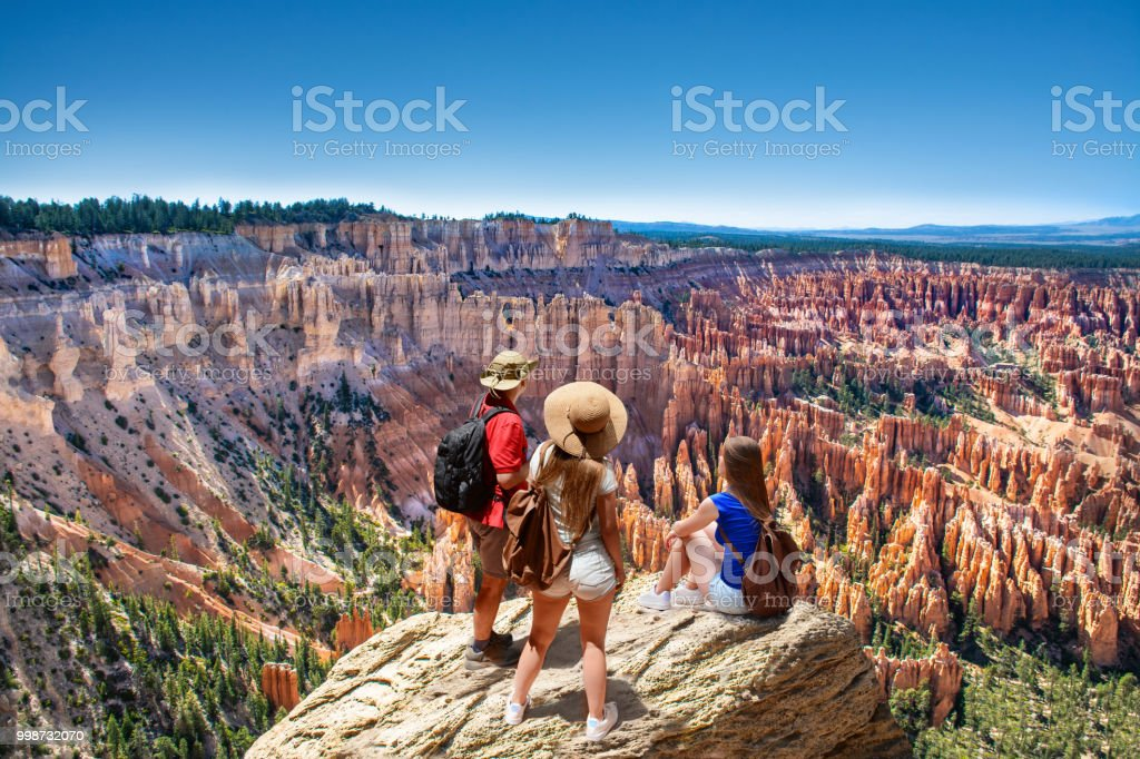Family on top of  mountain enjoying time together, looking at beautiful view. stock photo