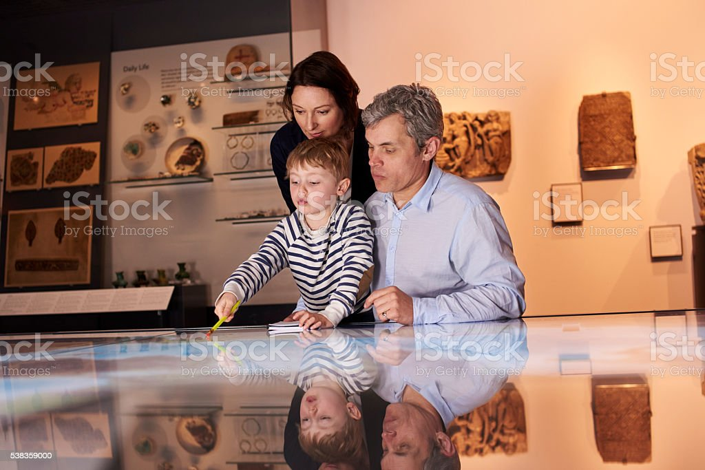 Family On Trip To Museum Looking At Map Together stock photo