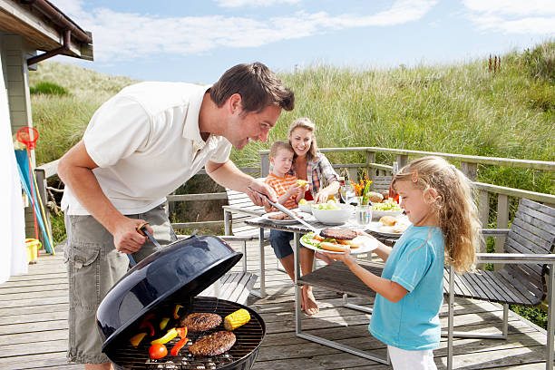 Family on vacation having barbecue stock photo