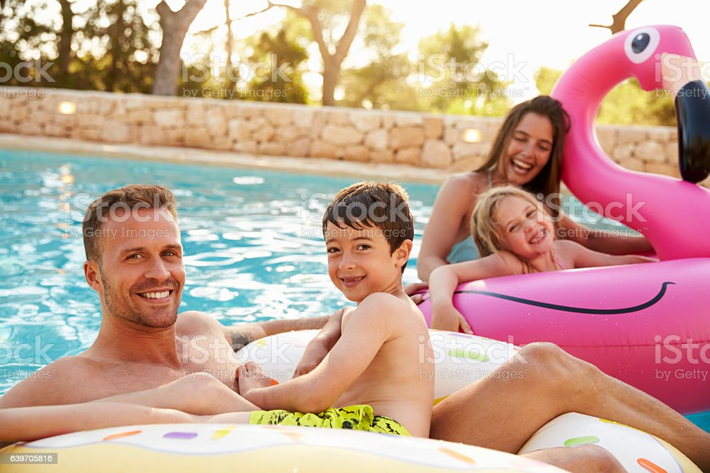 Family On Vacation On Inflatables In Outdoor Swimming Pool stock photo
