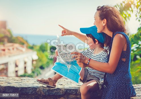 Mother and her son with a map and a camera, traveling in Europe  in summer