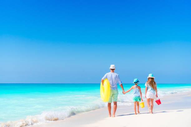 familie auf weißen tropischen strand auf karibik-insel. vater und töchter am ufer des meeres - urlaub in kuba stock-fotos und bilder
