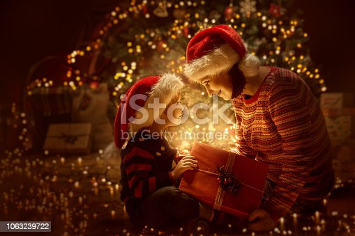 Family open Christmas Lighting Present Gift Box front of Xmas Tree, Happy Mother with Baby Child in Magic Night