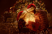 istock Family open Christmas Lighting Present Gift, Xmas Tree and Happy Mother Baby 1063239722
