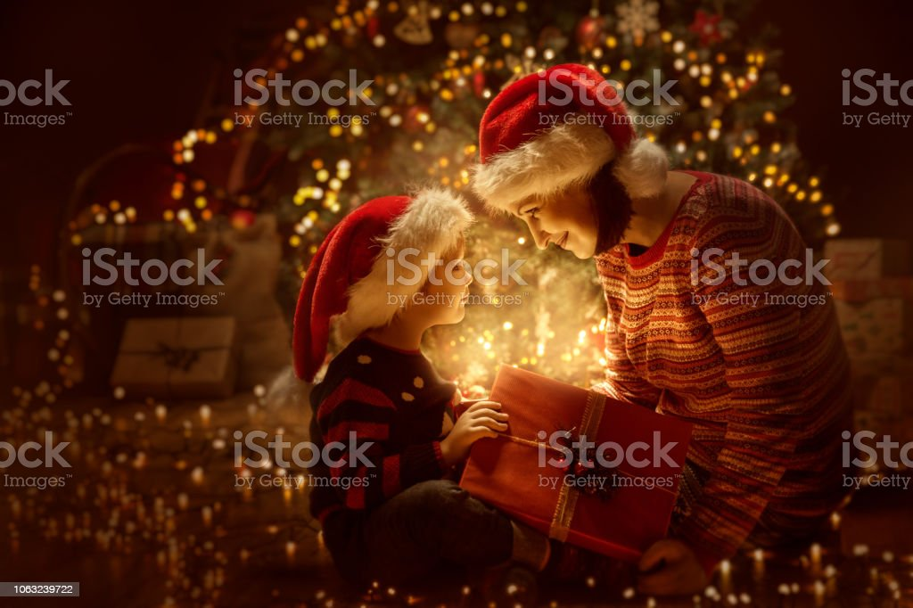 Family open Christmas Lighting Present Gift, Xmas Tree and Happy Mother Baby stock photo