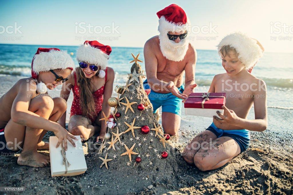 Family Opening Gift Under Sand Christmas Tree Stock Photo ...