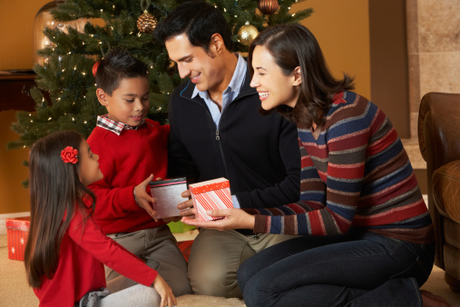 Family Opening Presents In Front Of Christmas Tree Stock ...