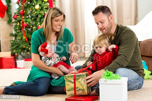 579124316 istock photo Family opens gifts on Christmas eve 547410528