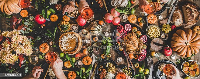 Family celebrating at Thanksgiving table. Flat-lay of feasting peoples hands with glasses of wine over Friendsgiving table with Autumn food, candles, roasted turkey and pumpkin pie over wooden table