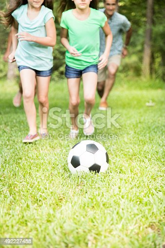 88688880 istock photo Family outdoors in spring, summer playing soccer game.  Park, yard. 492227488